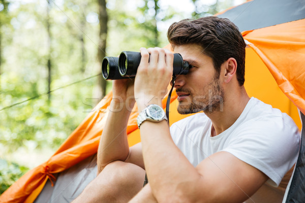 Man tourist sitting and looking at binoculars in forest Stock photo © deandrobot