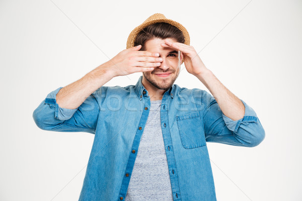 Happy young man covered one eye with hand and smiling Stock photo © deandrobot