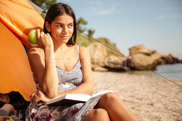 Girl eating apple and reading book at the beach camping Stock photo © deandrobot
