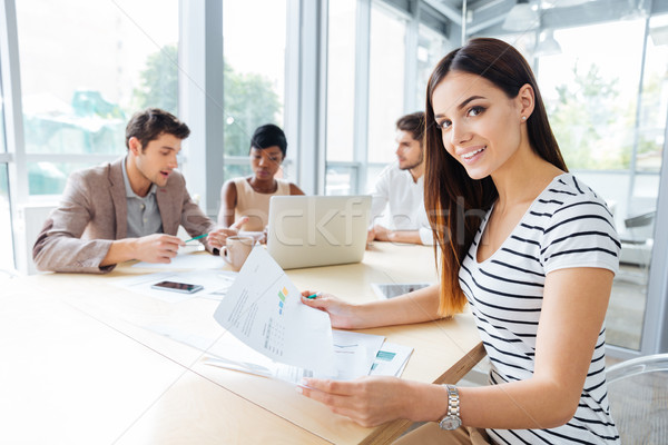 Happy woman creating presentation with her business team in office Stock photo © deandrobot
