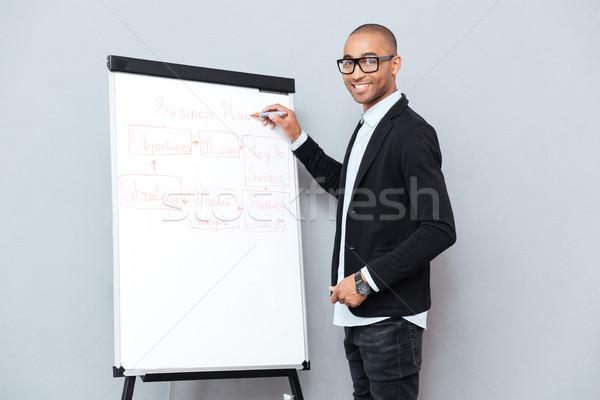 Sorridente africano homem óculos escrita negócio Foto stock © deandrobot