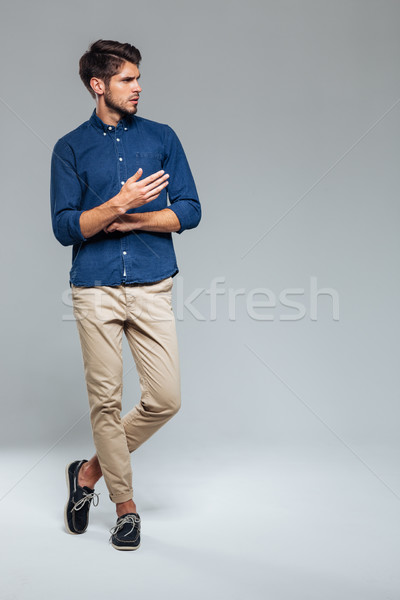 Full length portrait of a man standing with legs crossed Stock photo © deandrobot