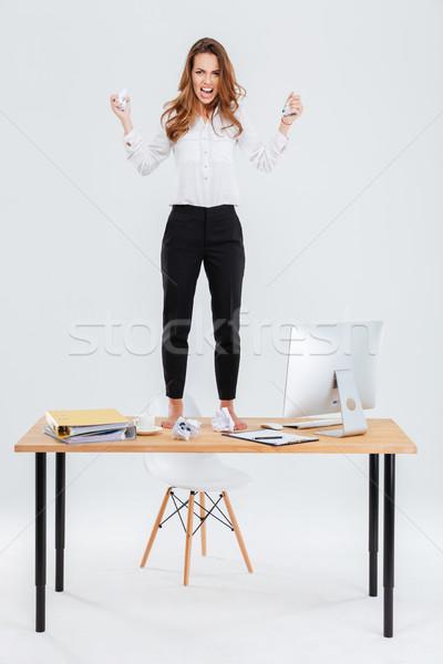 Dühös fiatal üzletasszony áll asztal dob Stock fotó © deandrobot
