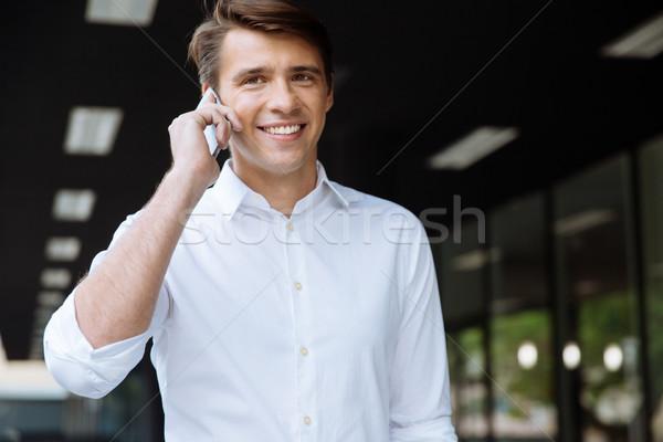 молодые бизнесмен говорить сотового телефона улице Сток-фото © deandrobot