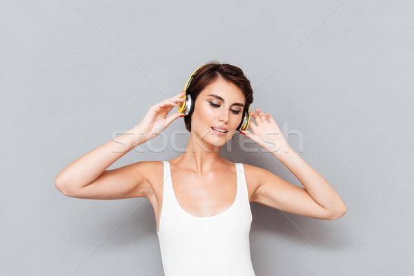 Belle brunette jeune femme écouter de la musique casque isolé Photo stock © deandrobot