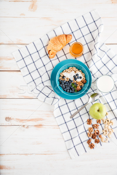 Oat cereals with berries and cream, cup of milk, apple Stock photo © deandrobot
