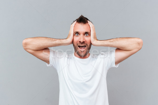 Stressed young man covers ears by hands and shouting Stock photo © deandrobot