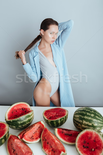 Attractive young woman in jacket and swimwear with cutted watermelons Stock photo © deandrobot