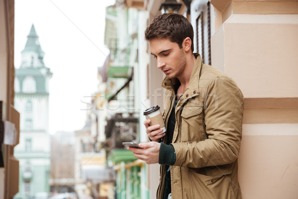 Man walking on street and chatting outdoors while drinking coffee Stock photo © deandrobot