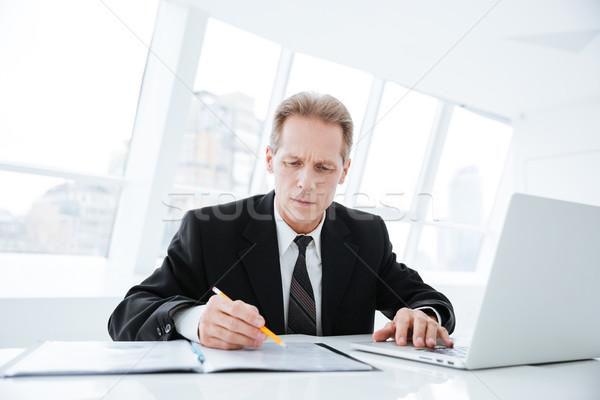 Elderly business man writing something Stock photo © deandrobot