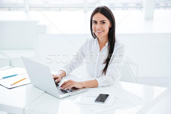 Vista laterale sorridere donna d'affari utilizzando il computer portatile guardando fotocamera Foto d'archivio © deandrobot