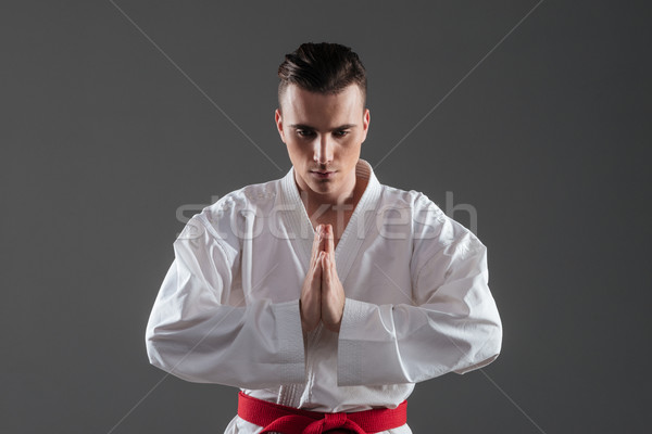 Handsome young sportsman dressed in kimono gesturing with hands Stock photo © deandrobot
