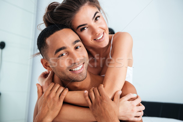 Portrait of happy beautiful young couple smiling and embracing Stock photo © deandrobot