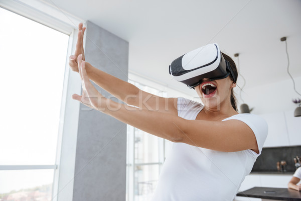 Woman playing computer games with virtual reality googles at home Stock photo © deandrobot