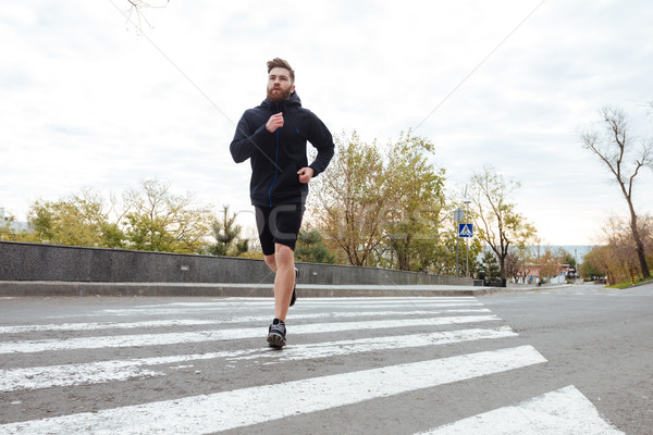 Young runner on crosswalk Stock photo © deandrobot