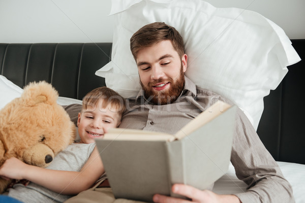 Boy lies near toy with his father reading fairytale book. Stock photo © deandrobot