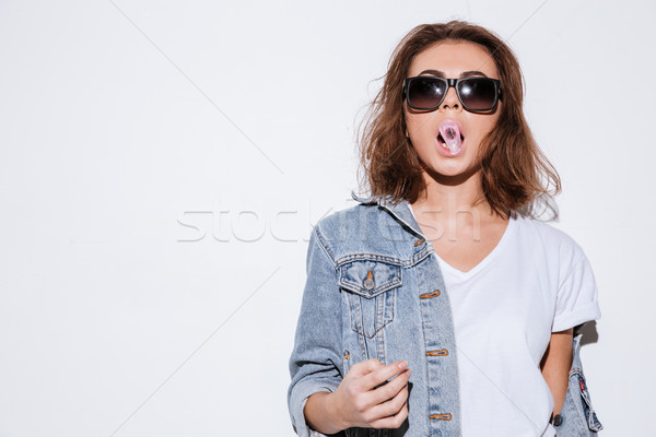 Woman blowing bubble with chewing gum. Stock photo © deandrobot