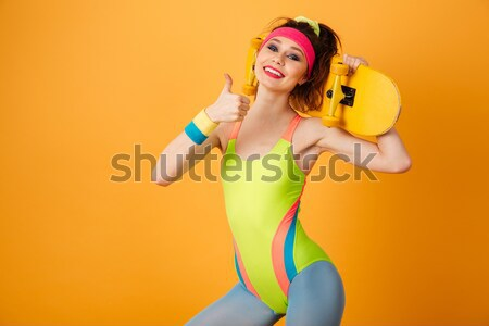 Cheerful beautiful young sportswoman standing and posing Stock photo © deandrobot