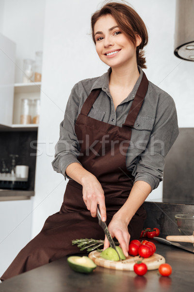 Cheerful lady standing in kitchen cut the avocado. Stock photo © deandrobot