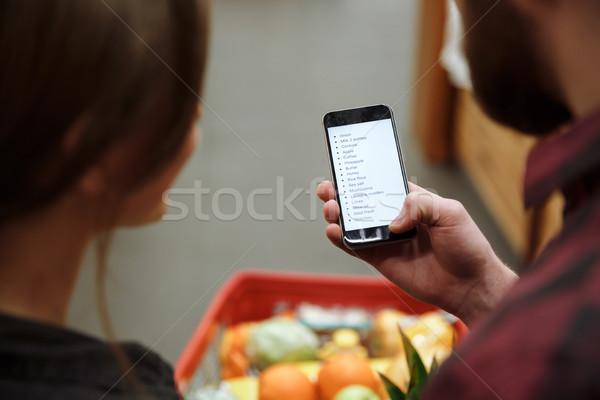 Amoroso Pareja pie supermercado mirando lista Foto stock © deandrobot