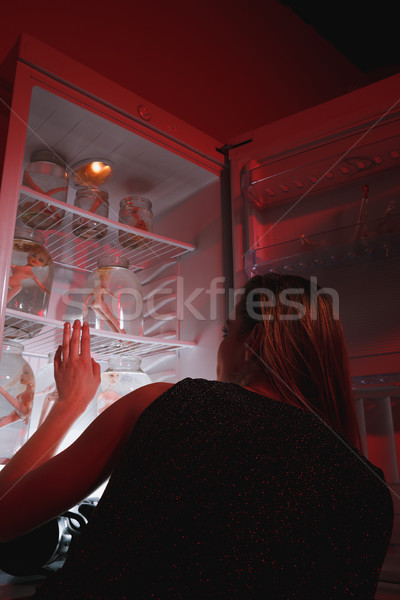Back view woman looking at fridge with dolls in jars Stock photo © deandrobot