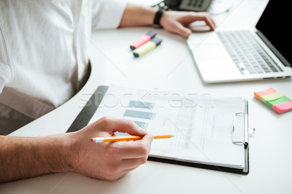 Cropped image of man writing something by the table Stock photo © deandrobot