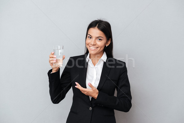 Business woman showing glass of mineral water in her hand Stock photo © deandrobot