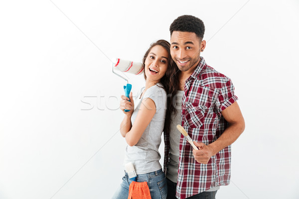 Portrait of couple with roller and brush Stock photo © deandrobot