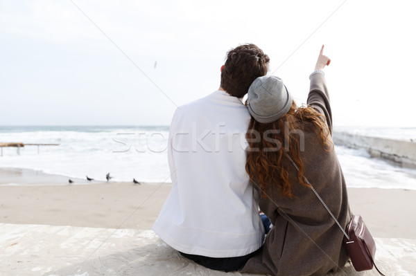 Back view of couple sitting on the beach in autumn Stock photo © deandrobot