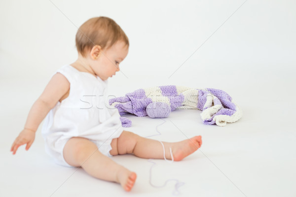 Little baby sitting on floor with plaid. Focus on plaid. Stock photo © deandrobot