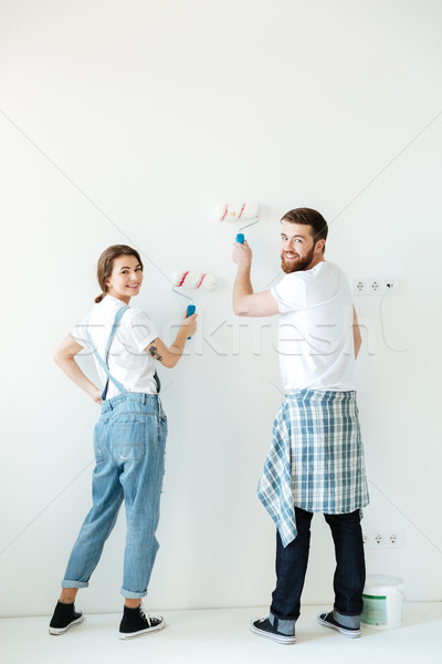 Full-length shot of lovers painting walls in new home Stock photo © deandrobot