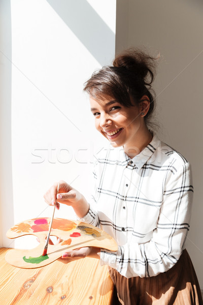 Smiling young woman artist holding palette and looking at camera Stock photo © deandrobot