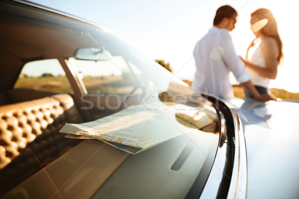 Young couple leaning on a car while standing outdoors Stock photo © deandrobot