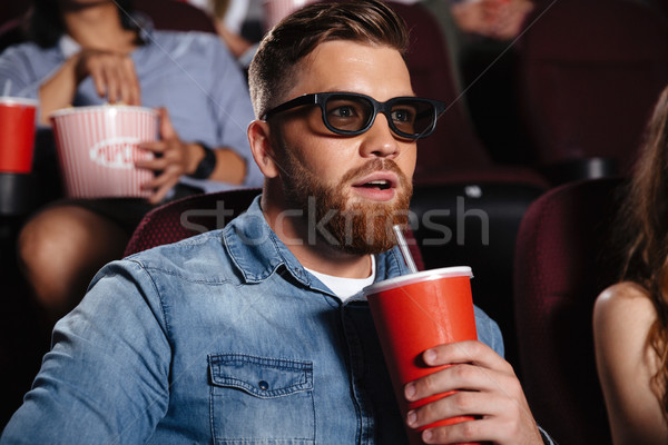 Concentrated young man sitting in cinema Stock photo © deandrobot