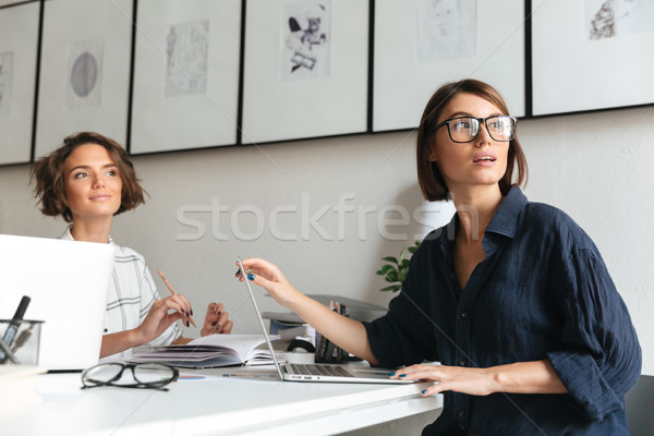 Side view of two pretty women sitting by the table Stock photo © deandrobot
