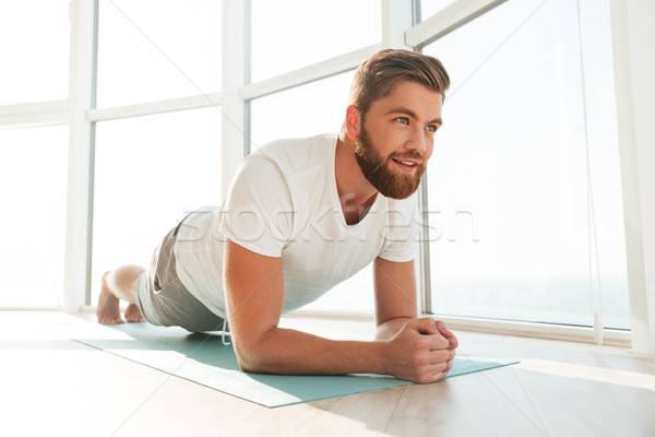 Smiling bearded man doing plank exercises over window background Stock photo © deandrobot