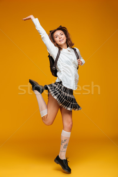 Full length portrait of a happy teenage schoolgirl in uniform Stock photo © deandrobot