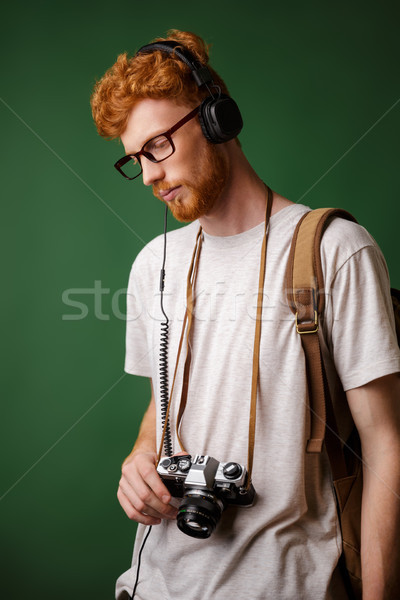 Yong readhead bearded hipster with backpack holding retro camera Stock photo © deandrobot