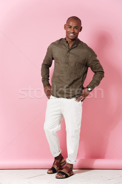 Full-length image of smiling african man holding arms on hips Stock photo © deandrobot