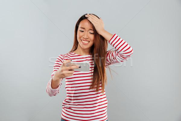 Nervioso jóvenes Asia dama jugar juegos Foto stock © deandrobot