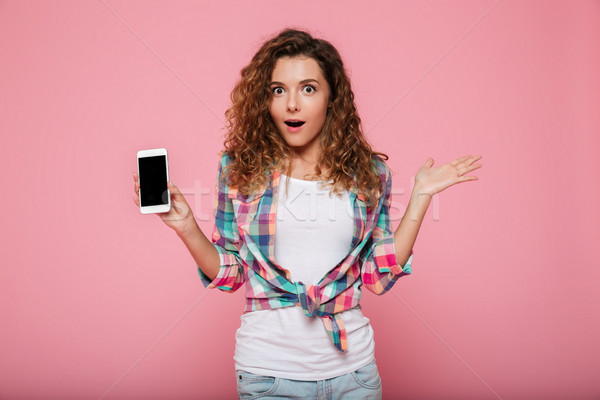 Surprised lady showing smartphone with blank screen isolated Stock photo © deandrobot