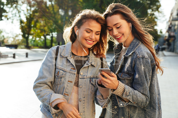 Two happy young brunette woman in jeans jacket listening to musi Stock photo © deandrobot