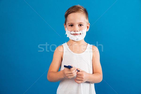 Smiling young boy in shaving foam holding razor Stock photo © deandrobot