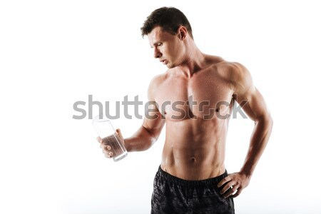 Concentrated young sportsman drinking water Stock photo © deandrobot