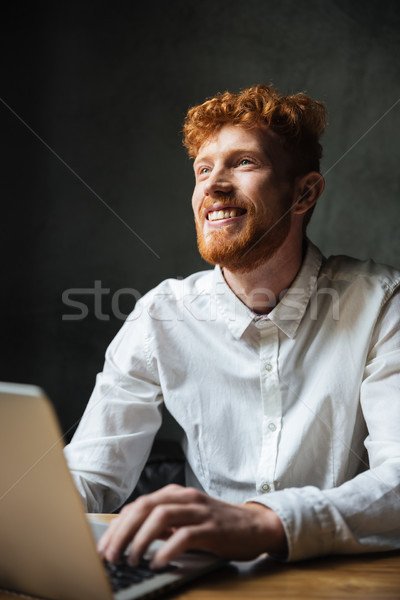 Portrait of a smiling young man typing on a laptop Stock photo © deandrobot