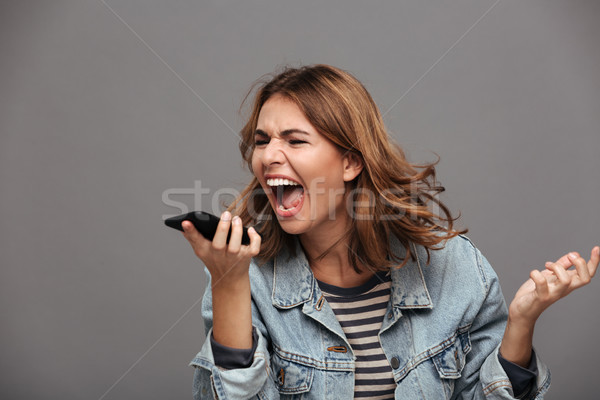 Portrait of a furious mad teenage girl Stock photo © deandrobot