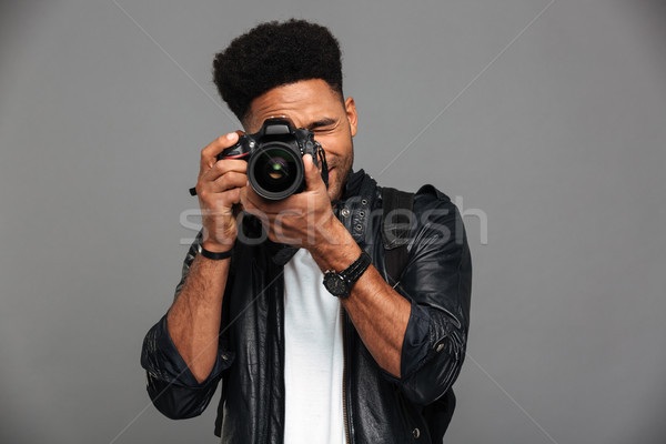 Handsome african guy with stylish haircut taking photo on digita Stock photo © deandrobot