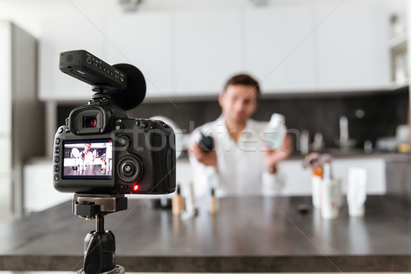 Handsome young man filming his video blog episode Stock photo © deandrobot