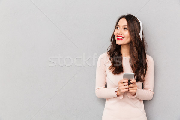Photo of pleased female smiling looking aside with silver smartp Stock photo © deandrobot