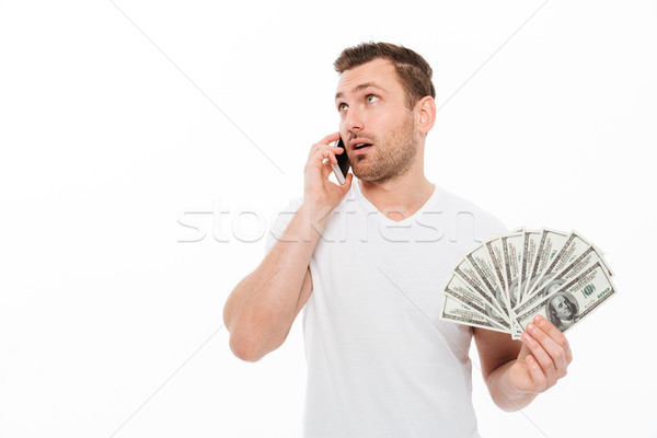 Concentrated young man talking by mobile phone. Stock photo © deandrobot